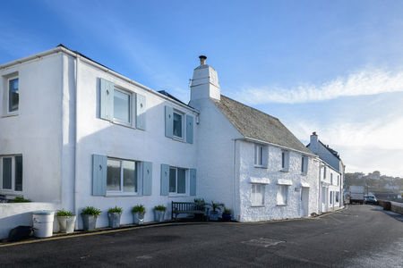 breakfast in bed: White painted houses on the Cornish coast in Cornwall, England. Stock Photo