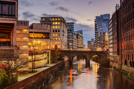 uk: Modern apartments on both side of river Irwell passing through Manchester city center, UK.