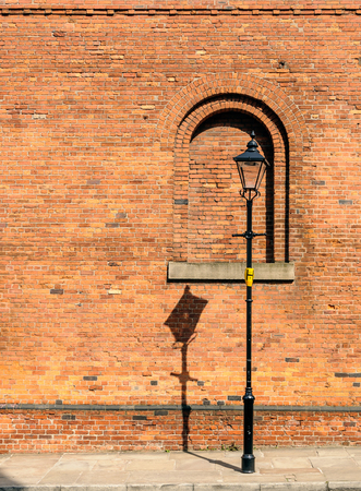 lamp post: A black lamp post with shadow on wall
