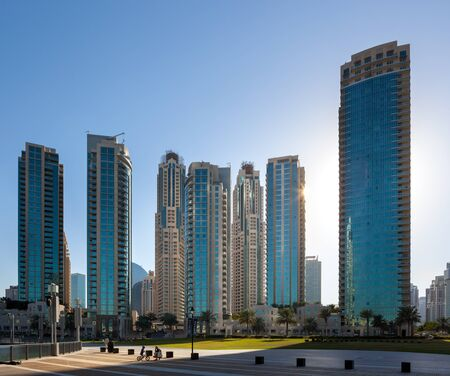 down town: Children playing in park infront of skyscrappers in down town dubai. Stock Photo