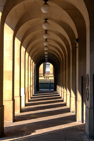 verticals: Sunlight coming through the arches forming shadows in columns. Stock Photo