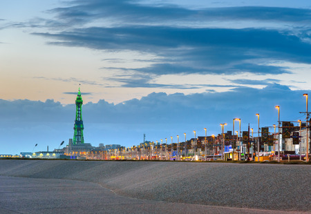 Blackpool tower illuminated in green light at the end of promenade. Stock Photo