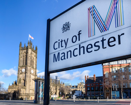 Sign board of Manchester city with Collegiate church in its background. Editorial