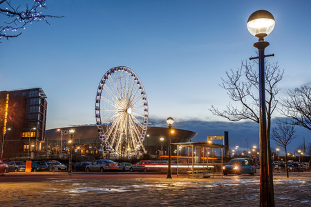 View of the ferris wheel outside the Echo Arena and cars in parking plot  in Liverpool, UK.