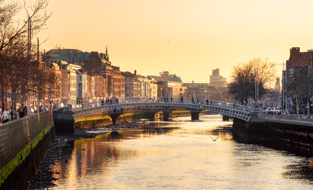 Ha'penny Bridge and the north banks of the river Liffey in Dublin City Centre view at sunset. Ha'penny Bridge is a pedestrian bridge built in 1816 of cast iron