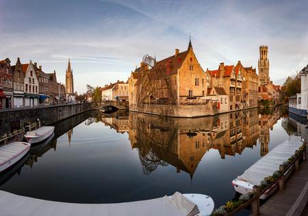 Belfry of Bruges reflected in the canal. Bruges, Flemish Region, Belgium