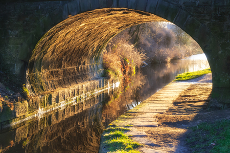 Sunrays enlightened the bridge tunnel over a canal in England.