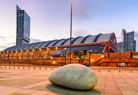 Beetham tower and Manchester train station besides a big rock lying on ground