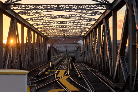 Train tracks on gravel, two of railways tracks merge with sunset background, Berlin Germany