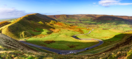Long and winding rural road of Winnat Pass  leading through green hills in the Peak District, UK