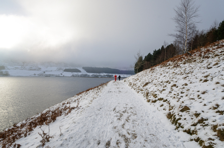 Tourists walking and their foot steps on snowy covered way at Dove stone reservoir, North West England.