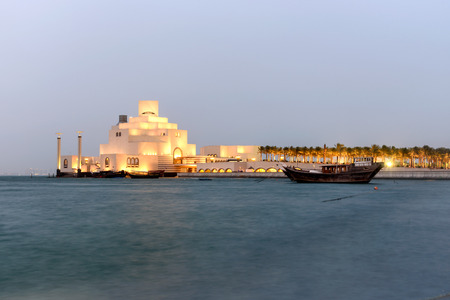 The museum of Islamic art  is built on an island off an artificial projecting peninsula near the traditional dhow (wooden Qatari boat) harbor. Stock Photo