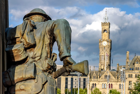 War Memorial Bradford UK depicting a bronze sculpture with city hall in its background