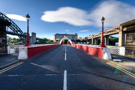 Footpath on either sides of the unique red painted swing bridge in Newcastle, UK Stock Photo