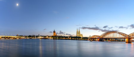 Hohenzollern bridge and Cologne's cathedral can be seen  along the riverside, and its twin towers protrude the cityscape Stock Photo