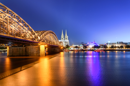 View to lighted cityscape with Cologne Cathedral and Hohenzollern Bridge, Cologne, Germany