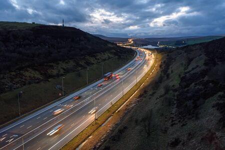 Sentieri di luce sulla M62 di notte vicino a Leeds, West Yorkshire, Regno Unito. Archivio Fotografico