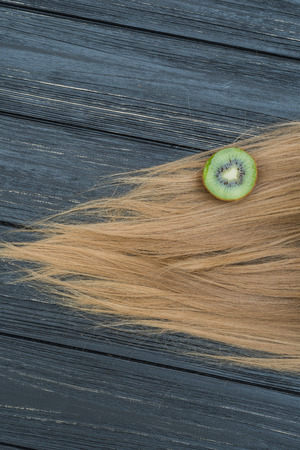 blond streaks: Kiwi and hair on grey wooden table