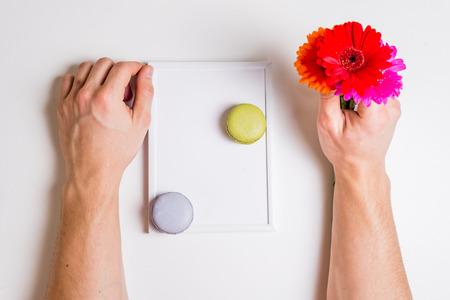 favor: colorful flowers in hand and macarons on white frame Stock Photo