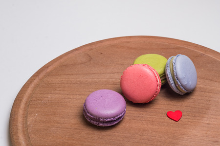 favor: Colorful French Macarons on brown wooden isolated white Stock Photo