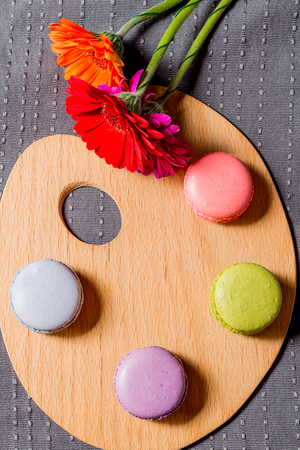 French macarons and colorful flowers on painting palette