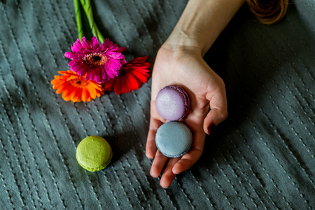 favor: colorful macaron in female hand and flowers Stock Photo