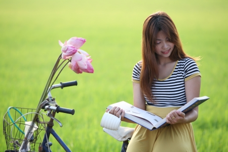 girl reading a book in paddy field  photo