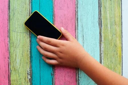 childrens hand touching smart phone. photo