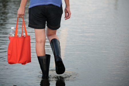 girl walking on flooded street,carrying fresh water for drinking photo