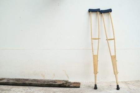 crutches at white wall  Archivio Fotografico
