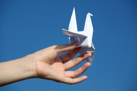 dove of peace: hand holding paper bird against blue sky