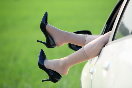 Woman legs out the windows in car with green paddy field background  photo