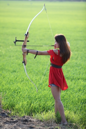 active arrow: girl drawing recurve bow in paddy field  Stock Photo