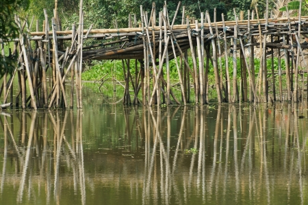 old bamboo bridge over river  photo