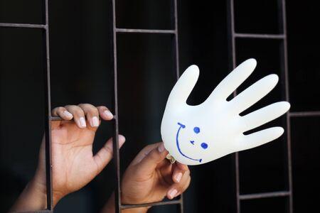 prisoner of war: hand in jail showing smiling glove  Stock Photo