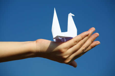 hand holding paper bird against blue sky  photo