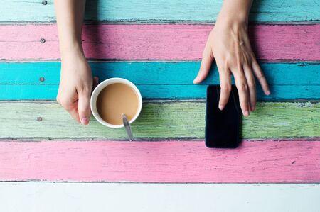 jolie fille: main tenant une tasse de caf� et utilisant un t�l�phone intelligent Banque d'images