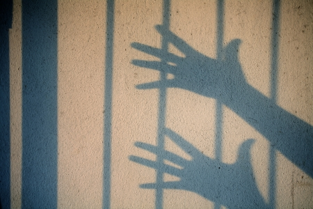 shadow of hand in jail  photo