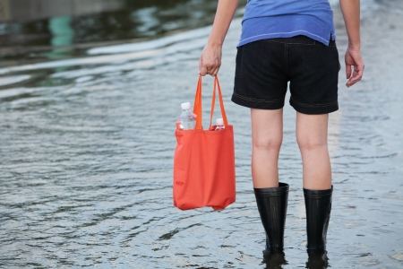 girl carrying fresh water for drinking on flooded street photo