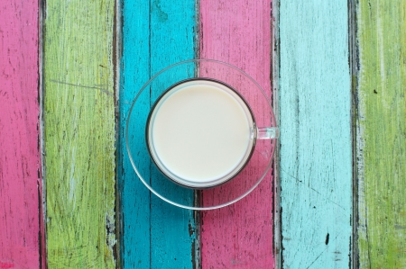 cup of milk on colorful wooden background  photo