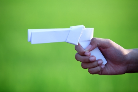 hand holding paper gun with green background  photo