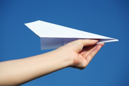 hand holding a paper airplane against a blue sky