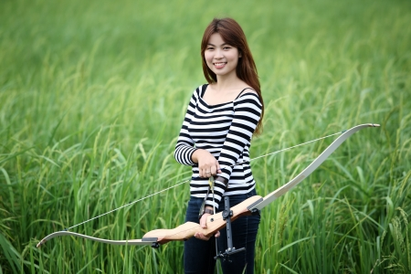 recurve: girl using recurve bow in paddy field  Stock Photo