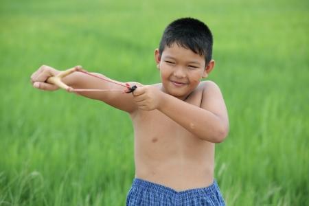 boy using slingshot  photo