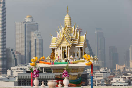 thai shrine among modern building  photo