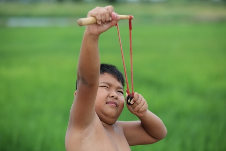 young boy aiming bird with slingshot  photo