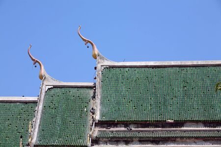 temple roof against blue sky,green tile made from beer bottle  photo