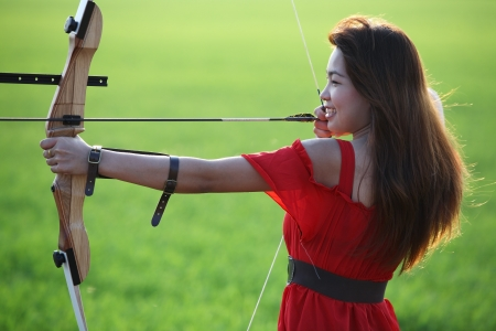 recurve: girl drawing a bow with green background