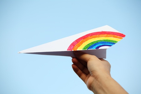 hand showing colorful paper airplane. photo