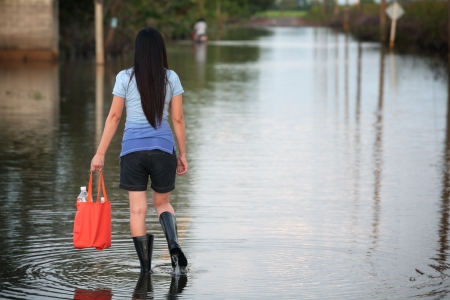 girl walking on flooded street,carrying fresh water for drinking Stock Photo